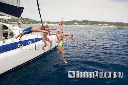 Happy friends jumping off catamaran into Caribbean Sea