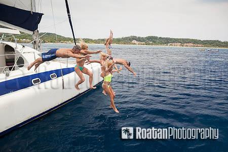 Happy friends jumping off catamaran