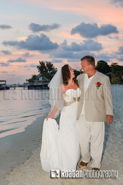 Bride and Groom laughing and walking along West Bay Beach after sunset