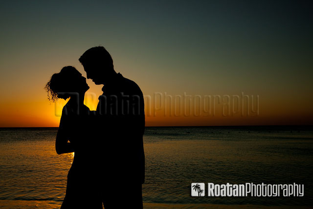 Silhouette of wedding couple kissing infront of sunset on West Bay Beach Roatan