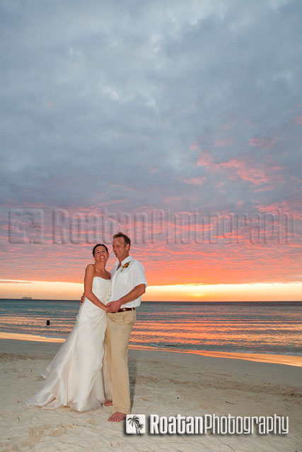 Wedding couple posing in front of sunset on West Bay Beach
