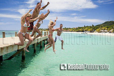 Group of friends jumping off dock stock photo
