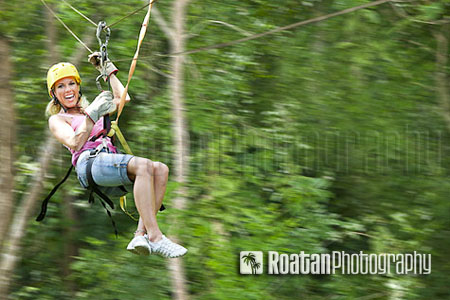 Confident woman flying through jungle on zipline stock photo
