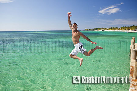 Excited man midair jumping into Caribbean Sea stock photo
