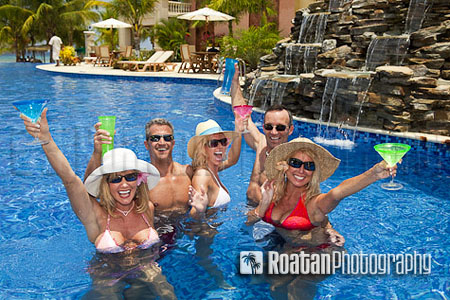 Five attractive adults enthusiasticly toasting in resort swimming pool stock photo