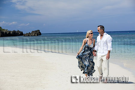 Happy mature couple walking on tropical beach stock photo