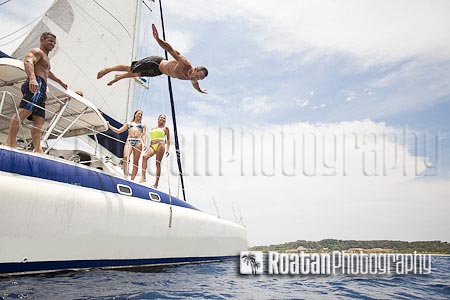 Man jumping off sailboat into Caribbean Sea stock photo