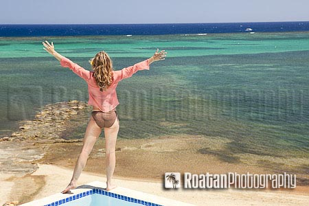 Woman with arms outstretched over sea view stock photo