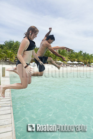 Couple jumping off dock into tropical sea