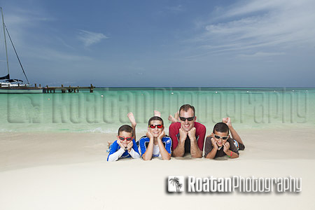 family beach portrait of father and sons resting on tropical beach stock photo