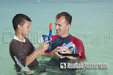Father teaching son to snorkel in tropical sea stock photo
