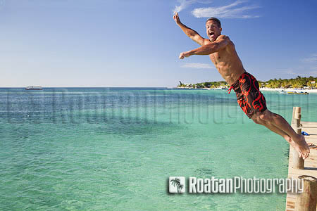 Man jumping off pier into caribbean sea stock photo