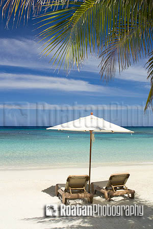 Two empty chairs on tropical beach looking out over Caribbean Sea stock photo